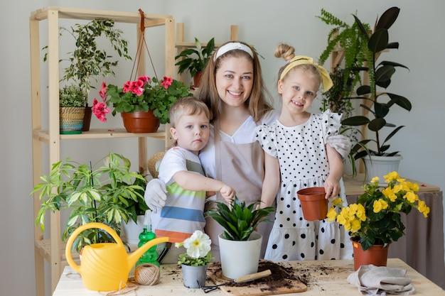 Mère avec son fils et sa fille petite aide par les tâches ménagères concept de jardinage domestique au printemps