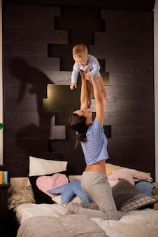 Mère avec son mignon petit fils jouant sur le lit