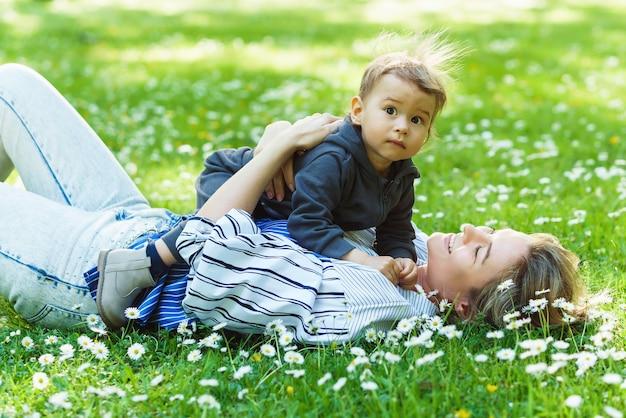Mère et son mignon petit garçon dans un champ de camomille