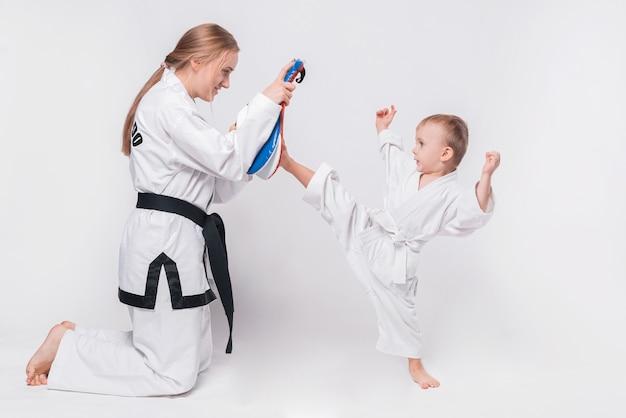 Mère son petit fils pratiquant les arts martiaux sur blanc
