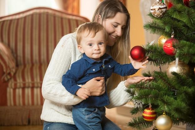 Mère avec son petit garçon de 10 mois décorant l'arbre de noël au living rom