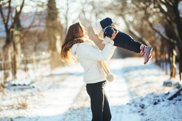 Mère avec son petit garçon dans les bras sur une route enneigée