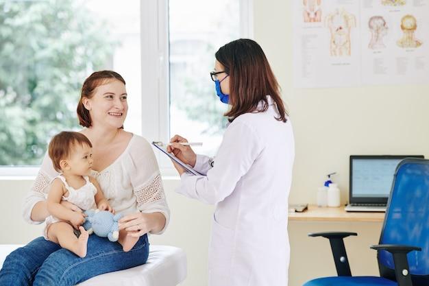 Mère souriante de l'adorable petite fille répondant aux questions du pédiatre en masque médical