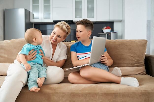Mère souriante avec deux fils de jouer sur le canapé