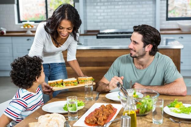 Mère souriante donnant des sandwichs à son fils et son mari