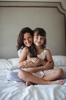 Mère souriante embrassant sa fille dans la chambre