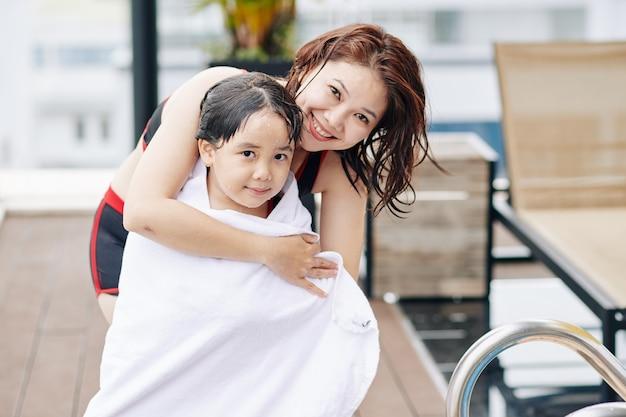 Mère souriante essuyant sa petite fille avec une grande serviette douce après la baignade dans la piscine