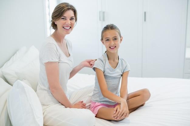 Mère souriante peignant les cheveux des filles sur le lit dans la chambre à la maison