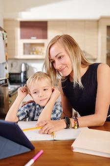Mère souriante pointant sur une tablette pour expliquer la leçon à son enfant qui étudie à la maison