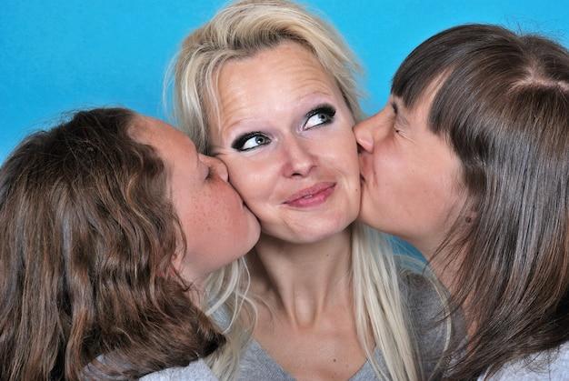 Une mère sourit alors qu'elle reçoit un baiser sur la joue d'elle toi