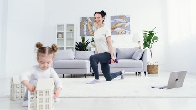 Mère sportive faisant des exercices avec des haltères et sa jolie fille tendre jouant avec des jouets au premier plan.