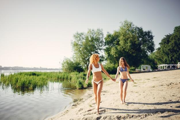 Mère sportive avec jolie fille marchant près du lac