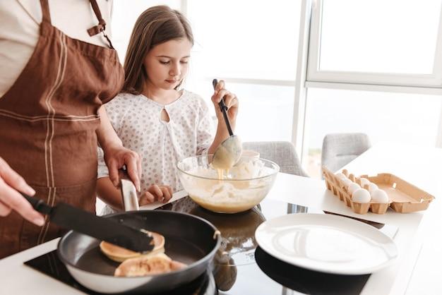 Mère en tablier et fille 8-10 cuisiner ensemble, et faire frire des crêpes sur une cuisinière moderne dans la cuisine