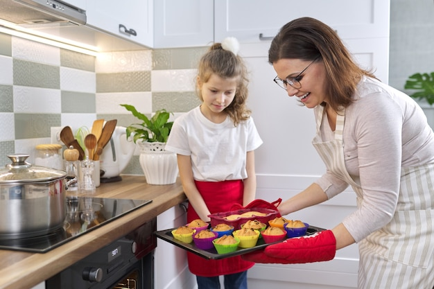Mère en tablier et fille petite assistante préparant des cupcakes ensemble. femme sortant un plateau avec des cupcakes cuits au four, cuisine intérieure à la maison. famille, fête des mères, cuisine saine faite maison