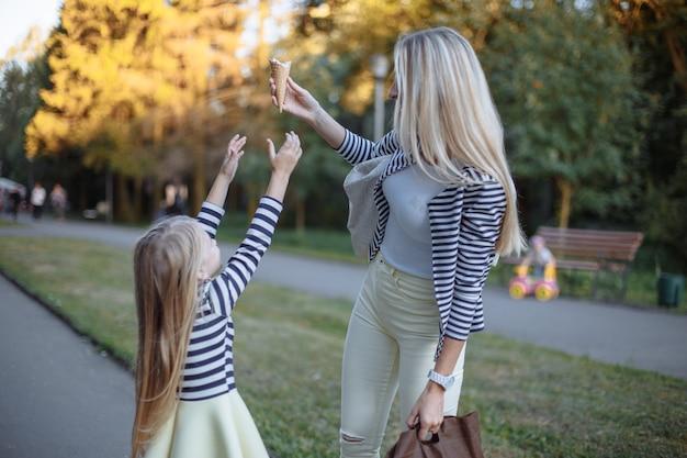 Mère tenant un cornet de crème glacée pendant que sa fille essaie de le ramasser