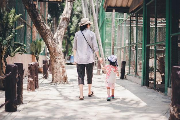 Mère tenant une petite main d'enfant et se promener dans le zoo pour voir des animaux