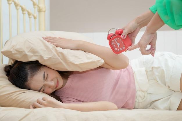 Mère tenant le réveil et se réveiller sa fille adolescente