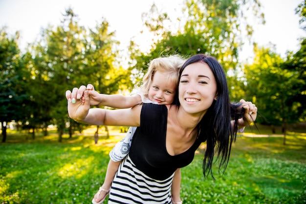 Mère Tenant Sa Fille à L'extérieur En Souriant. Heureuse Mère Et Fille Marchant Dans Le Parc Photo Premium