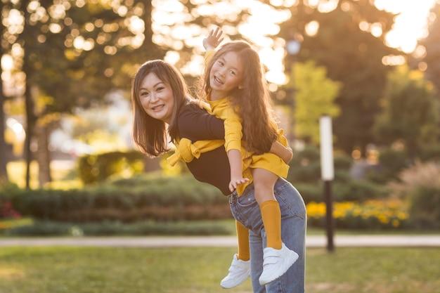 Mère tenant sa fille sur son dos
