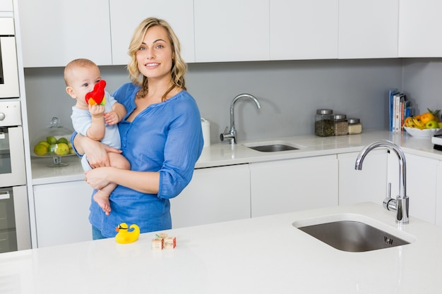 Mère tenant son bébé dans la cuisine