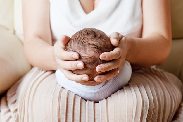 Mère tenant la tête de son fils nouveau-né dans les mains. le bébé sur les mains à maman. mère aimante main tenant mignon bébé nouveau-né endormi