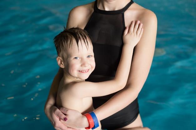Mère tient dans ses bras un petit garçon dans la piscine