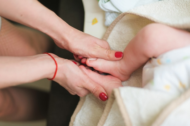 Mère tient des pieds de bébé nouveau-né