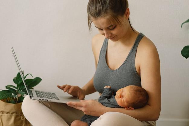 La mère tient son fils nouveau-né et travaille à l'ordinateur à la maison
