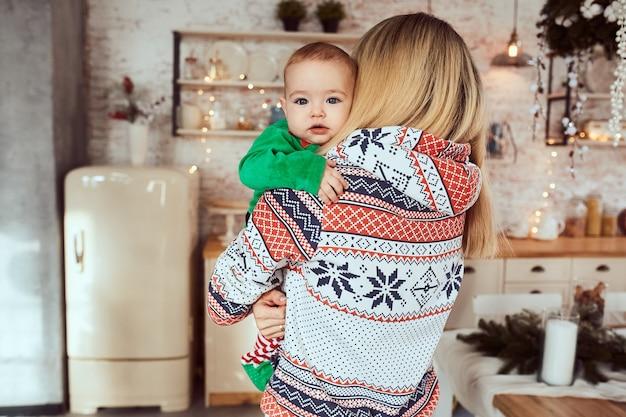 Mère tient son mignon petit fils sur les mains