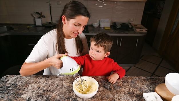 Mère et tout-petit garçon cuisson des biscuits de noël