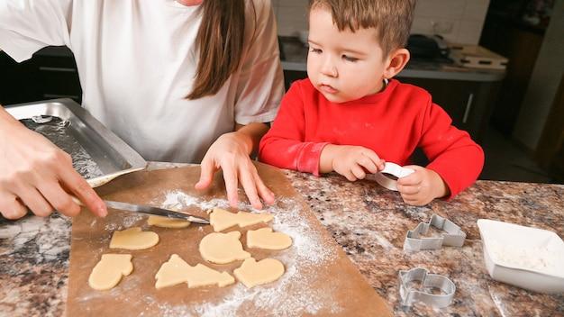 Mère et tout-petit garçon faire des biscuits de noël sur la cuisine