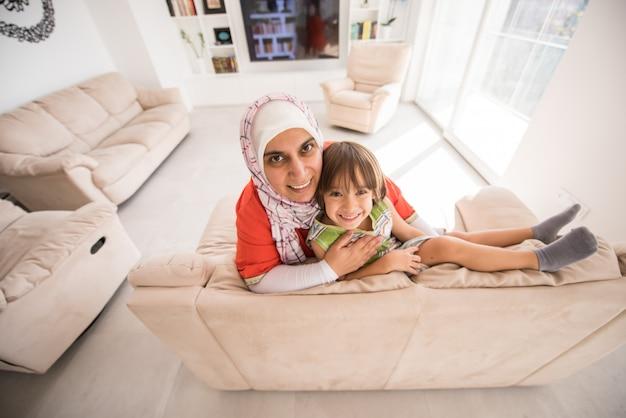 Mère traditionnelle musulmane avec petit fils mignon à la maison dans le salon