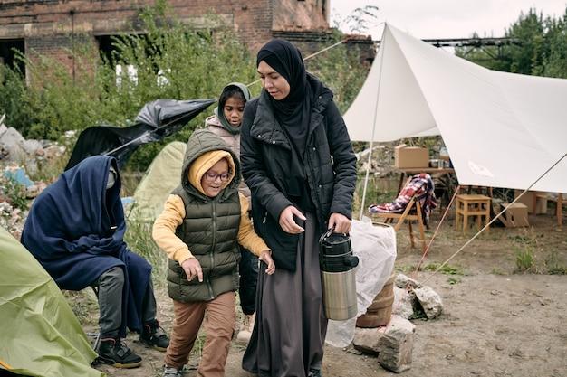 Mère transportant une bouteille thermos le long d'un camp de réfugiés