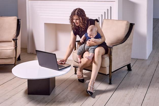 La mère travaille à distance avec un ordinateur portable avec un bébé à l'intérieur