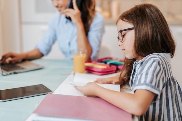 La mère travaille à domicile à cause du coronavirus pendant que sa fille fait ses devoirs.