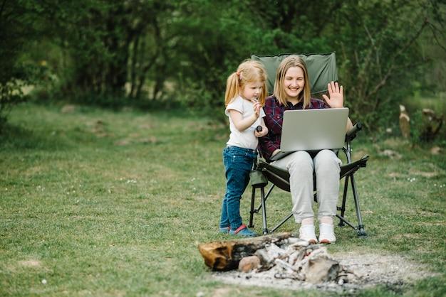 Mère travaille sur internet avec enfant à l'extérieur
