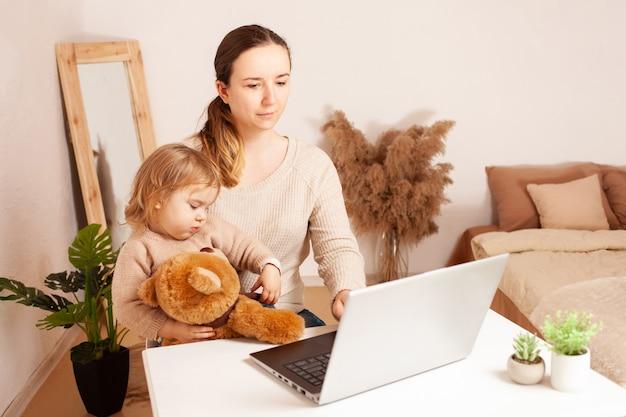 Mère travaille à la maison pour un ordinateur portable l'enfant empêche le travail une jeune femme est indépendante avec elle