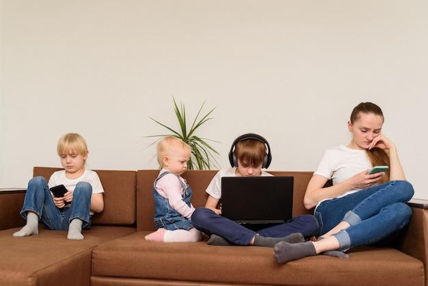 Mère et trois enfants sont assis sur un canapé et utilisent un téléphone et un ordinateur portable. dépendance aux personnes et à la technologie