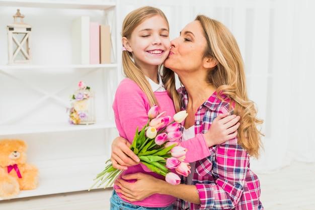 Mère avec des tulipes embrassant sa fille sur la joue