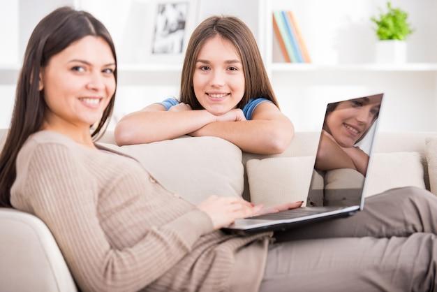 La mère utilise un ordinateur portable assis sur un canapé.
