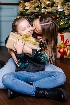 Mère va faire une surprise pour sa fille donne un cadeau, près de l'arbre de noël à la maison.