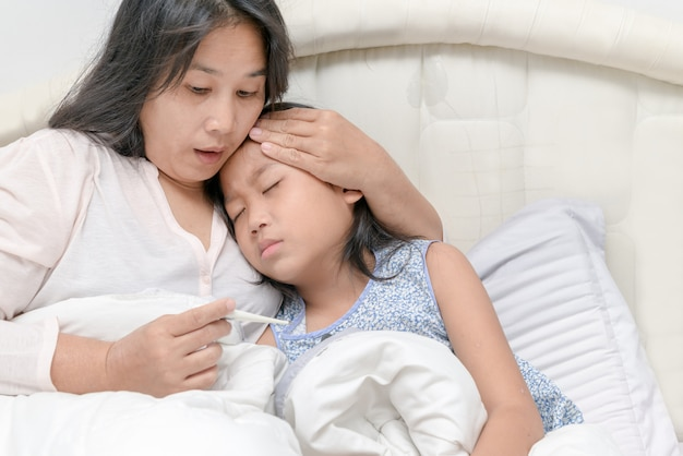 Mère vérifiant la température de sa fille malade.