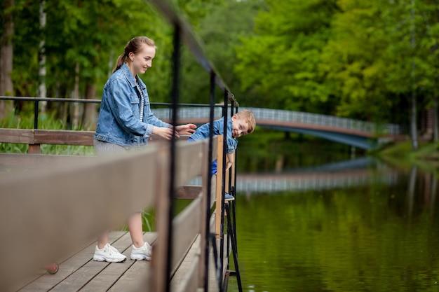 La mère vit que l'enfant tombera dans l'eau. un petit garçon monte une balustrade de pont