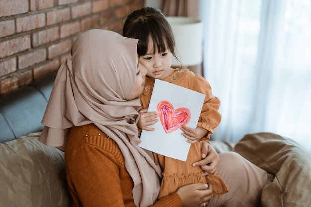 Mère voilée a embrassé la petite fille tout en étreignant et en tenant le papier imprimé coeur