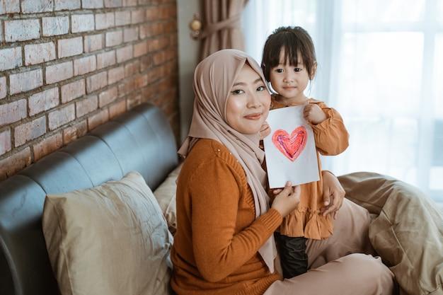 Mère voilée et petite fille sourire tout en tenant du papier avec une photo de coeur comme symbole de l'amour