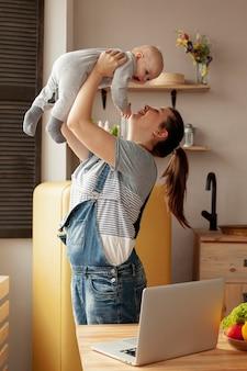 Mère vue de face avec bébé à la maison