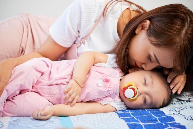 Mères embrassant sa fille endormie