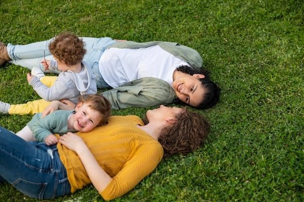 Les mères lgbt à l'extérieur dans le parc avec leurs enfants se détendre sur l'herbe