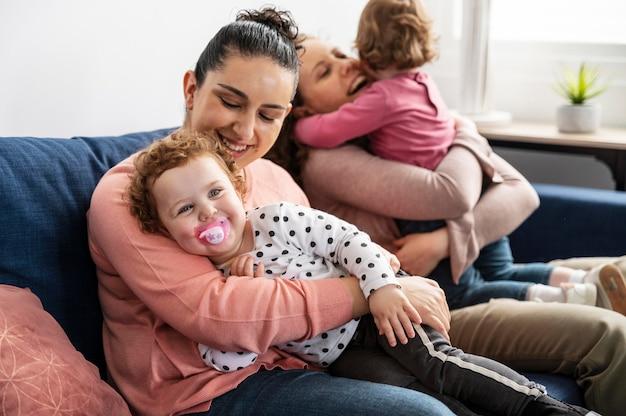 Mères lgbt à la maison sur le canapé avec des enfants
