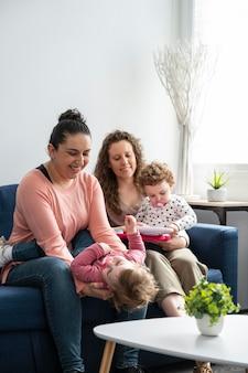 Mères lgbt à la maison sur le canapé jouant avec leurs enfants